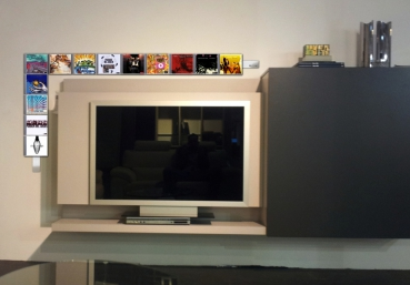 The image shows several horizontally arranged side by side CD CD Wall1x3 wall shelves next to the flat screen mounted